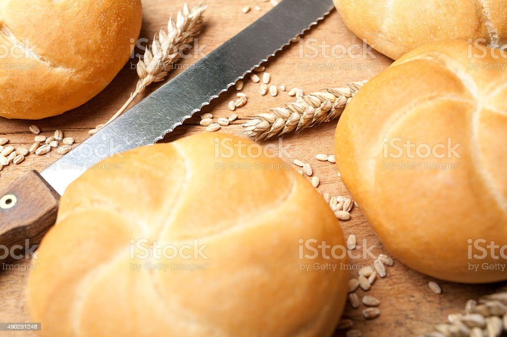 Knife and kaiser rolls on cutting board stock photo