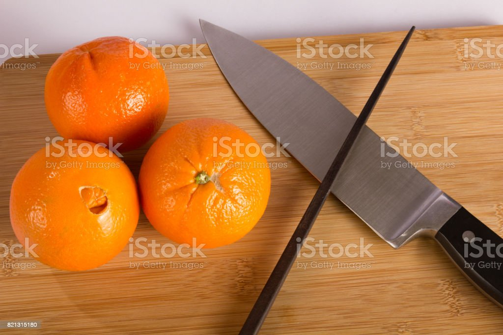 Knife and Oranges on Cutting Board with Chopstick stock photo