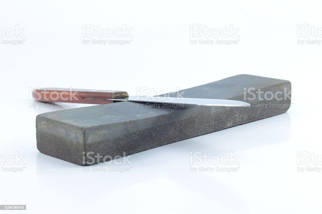 Knife and whetstone isolated stock photo