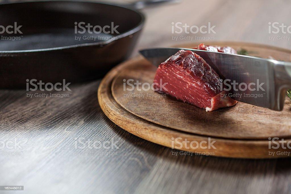 Knife cuts the tenderloin fillet into steaks royalty-free stock photo