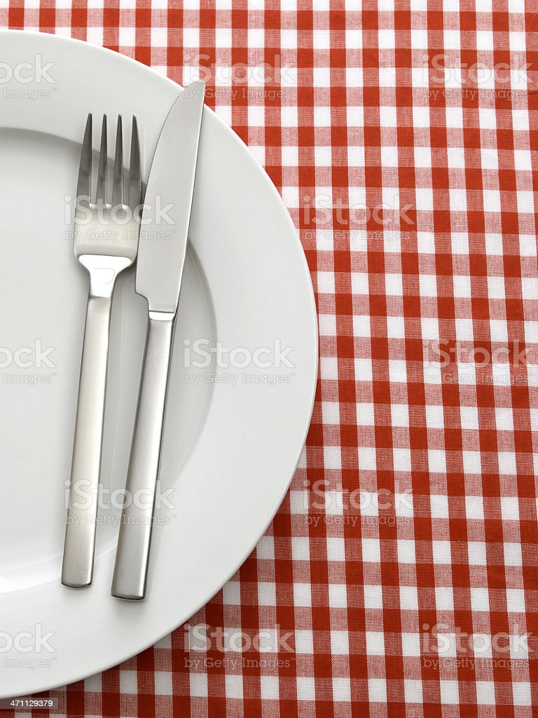knife fork and plate on tablecloth royalty-free stock photo