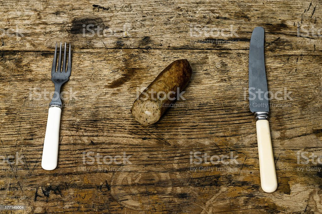 Knife, fork and sausage on wooden table royalty-free stock photo