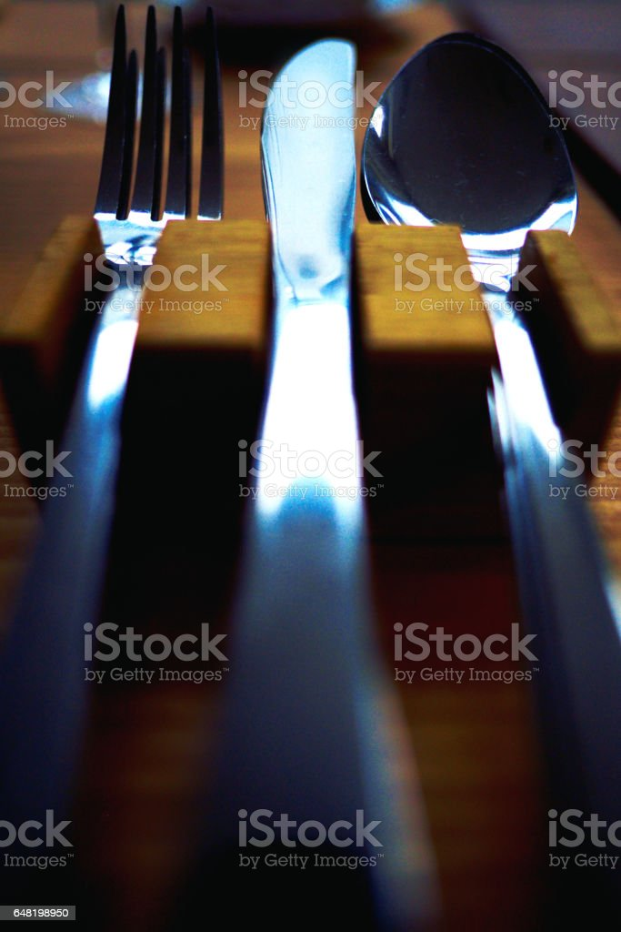 knife, fork and spoon close up on wooden holder stock photo