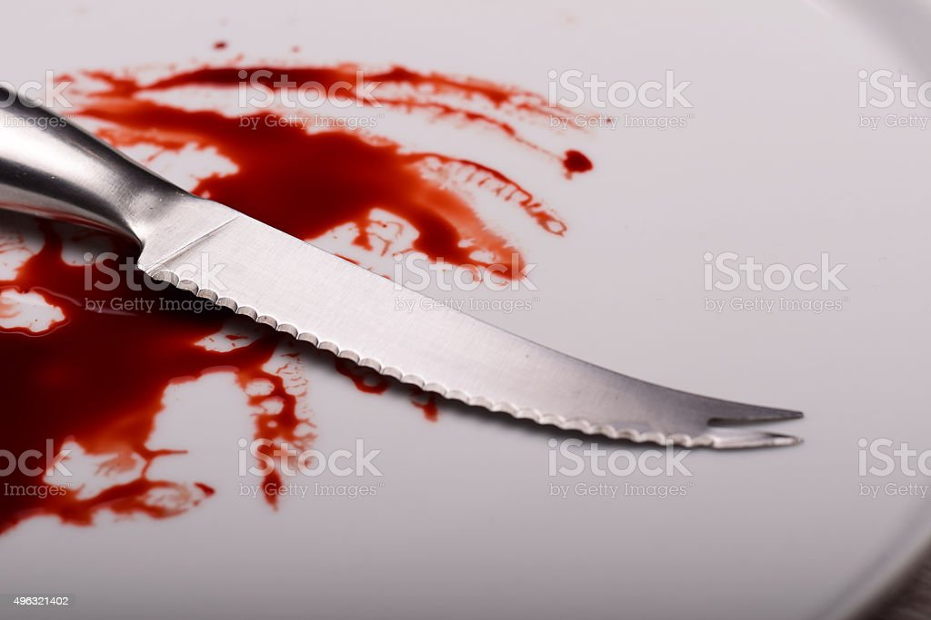 Knife on white plate with blood stock photo