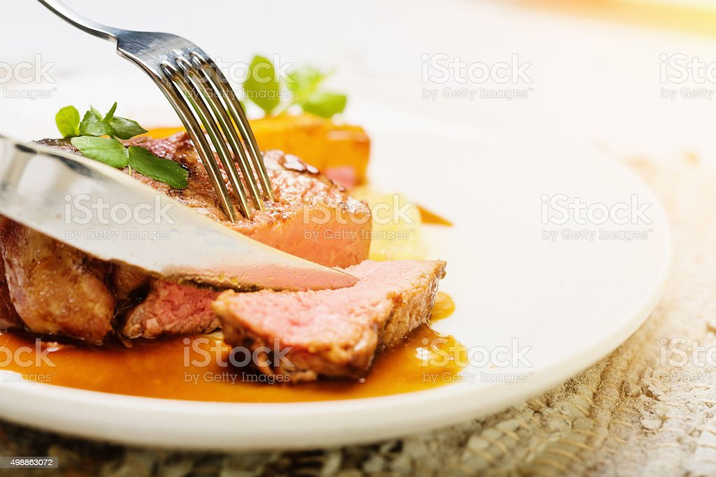 Knife slices juicy grilled fillet steak stock photo