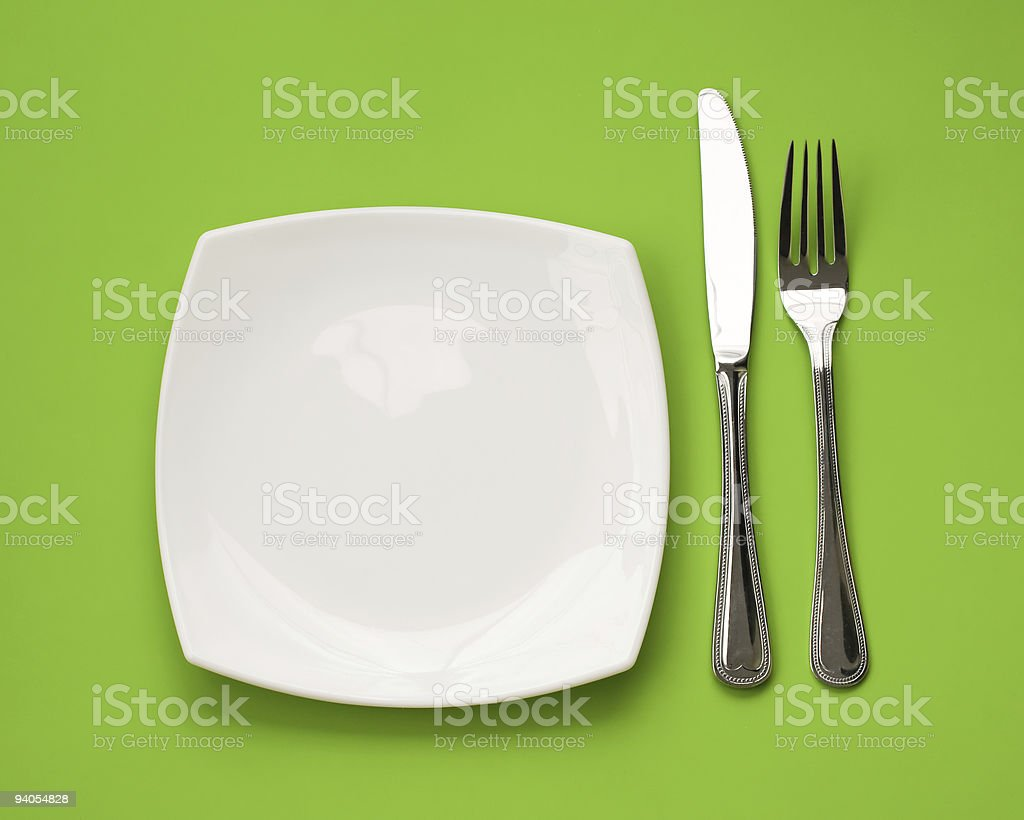 Knife, square white plate and fork on green royalty-free stock photo