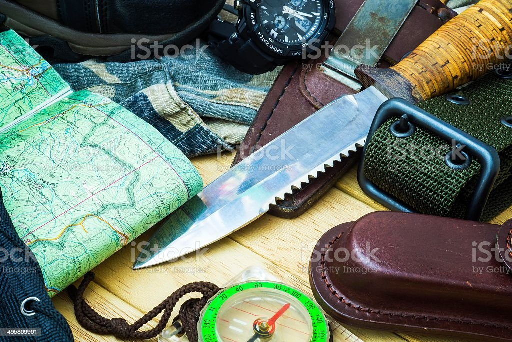 Knife surrounded by tourist equipment stock photo