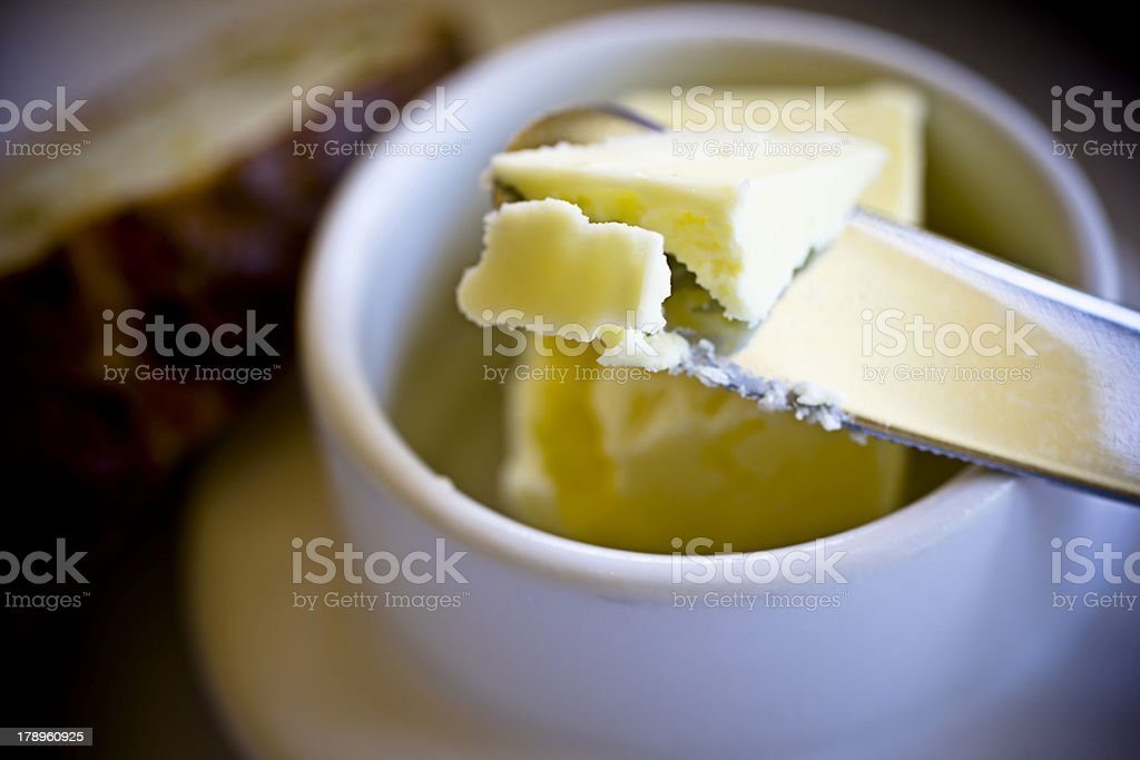 Knife taking ready-to-spread butter from a crock stock photo