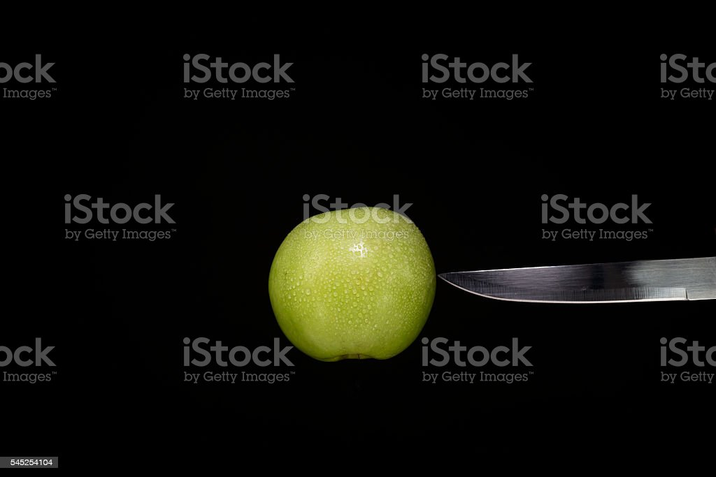 Knife to stab the apple and black background . stock photo