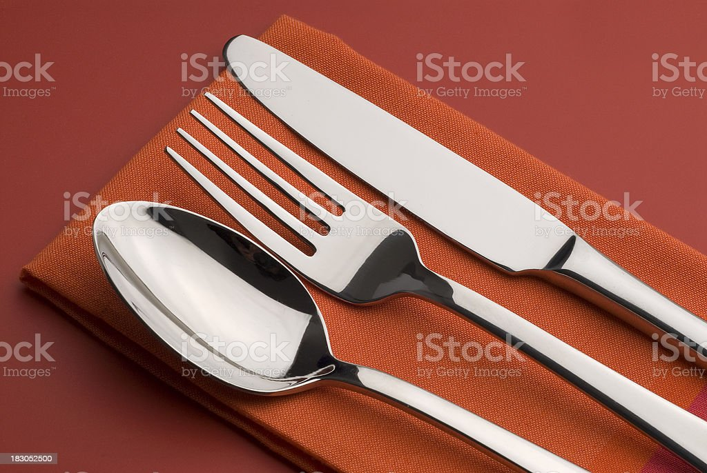 Knife,fork and spoon on a red background royalty-free stock photo