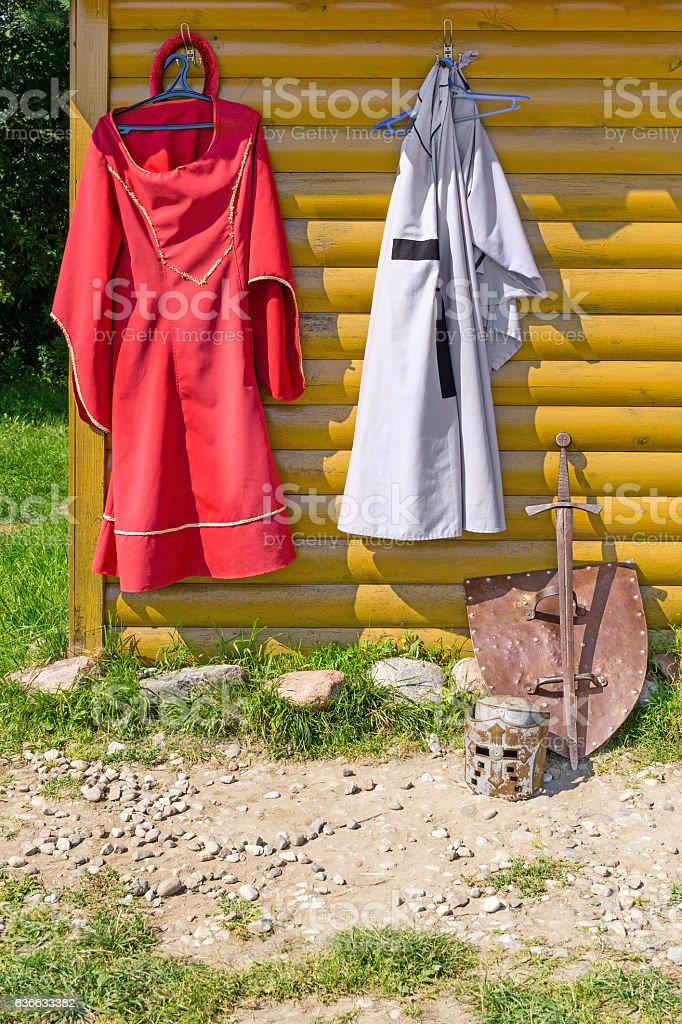 Knight cloak and dress on wooden wall stock photo