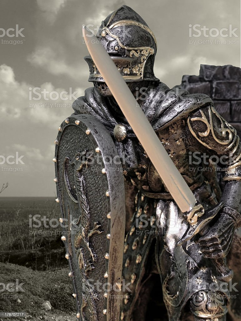 A knight dressed in ornate armor with sword and shield stock photo