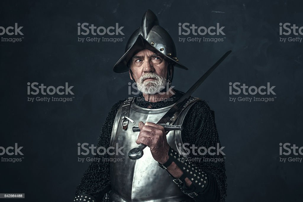 Knight in armor with gray beard holding sword. stock photo