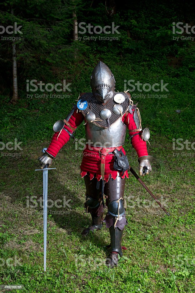 Knight in Armor With Helmet and Sword in the Forest stock photo