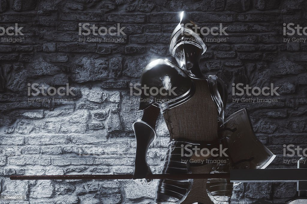 Knight in armour standing in castle room stock photo