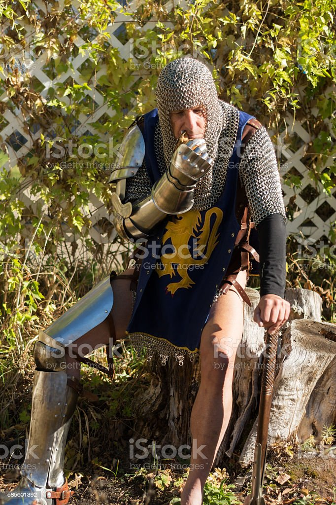 Knight in partial armour full length sitting outdoors, colour. stock photo