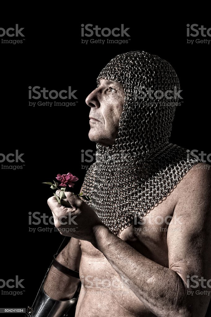 Knight in partial armour holding rose, looking up to light. stock photo