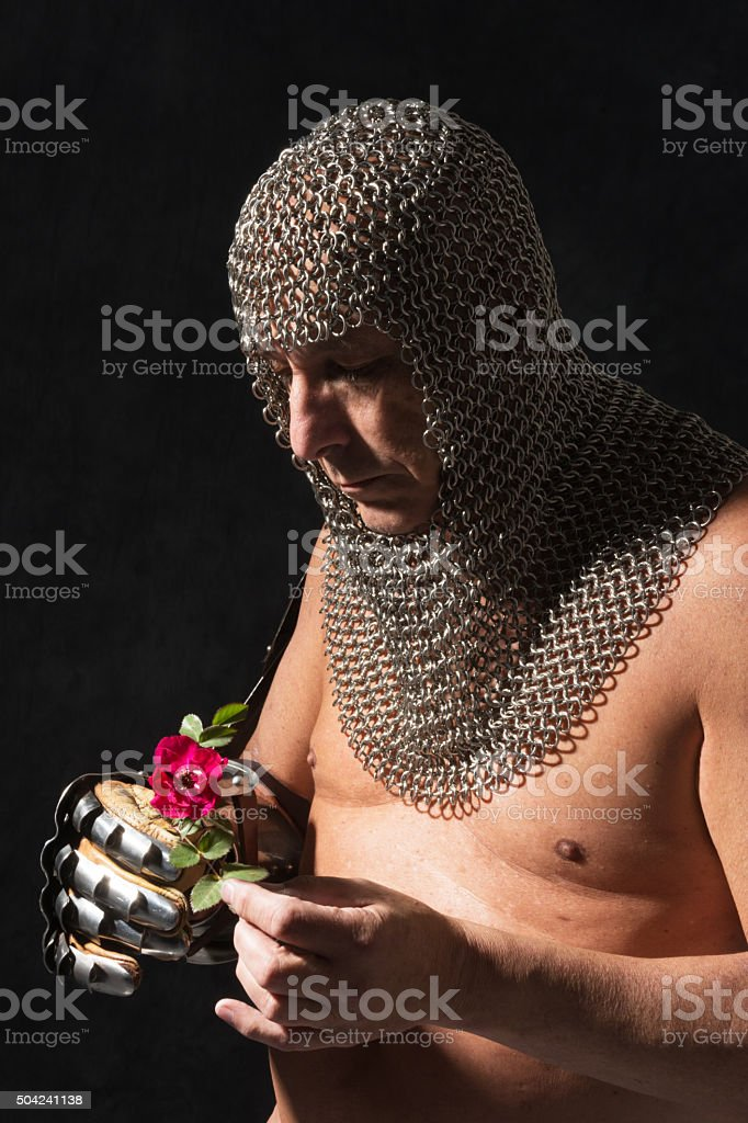Knight in partial armour holding rose, studio shot on black. stock photo