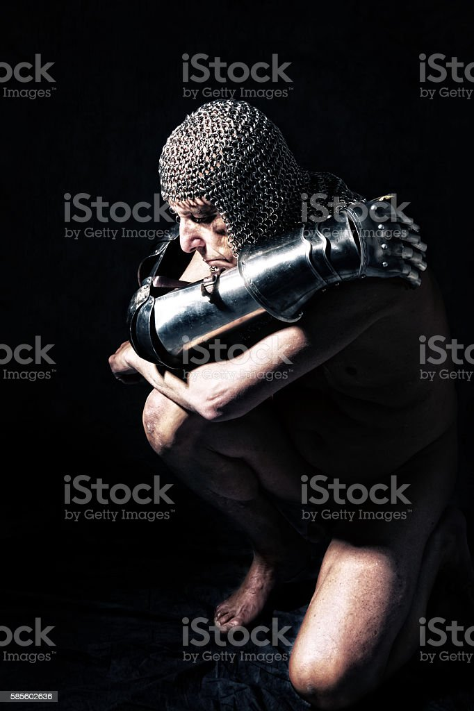 Knight in partial armour kneeling with arms around self. stock photo