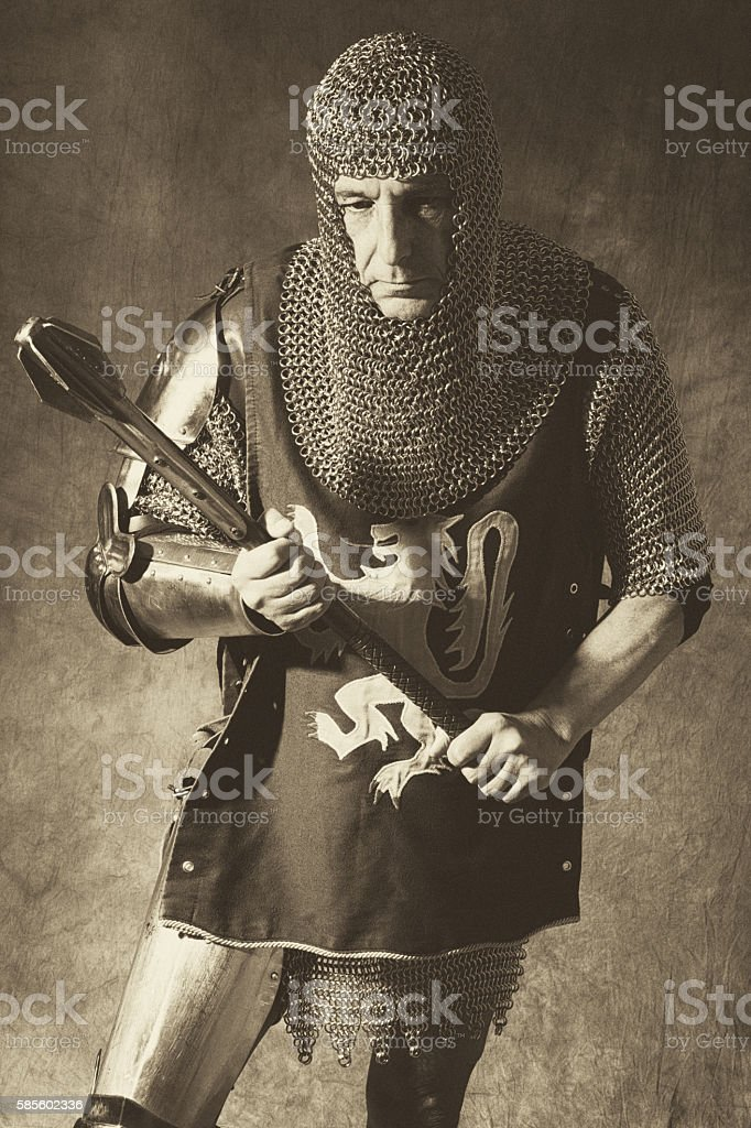 Knight in partial armour standing with mace, three quarter length. stock photo