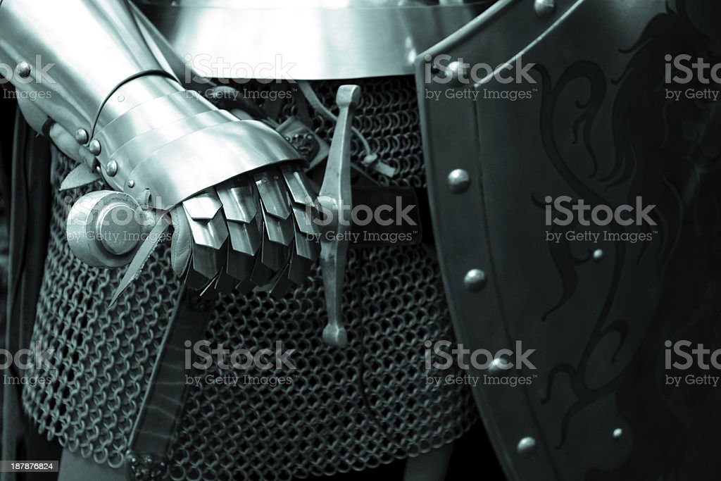 A knight in steel armor posing with his sword and shield stock photo