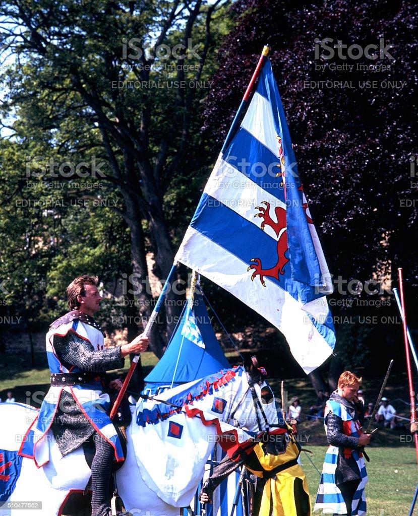 Knight on horseback holding a flag. stock photo