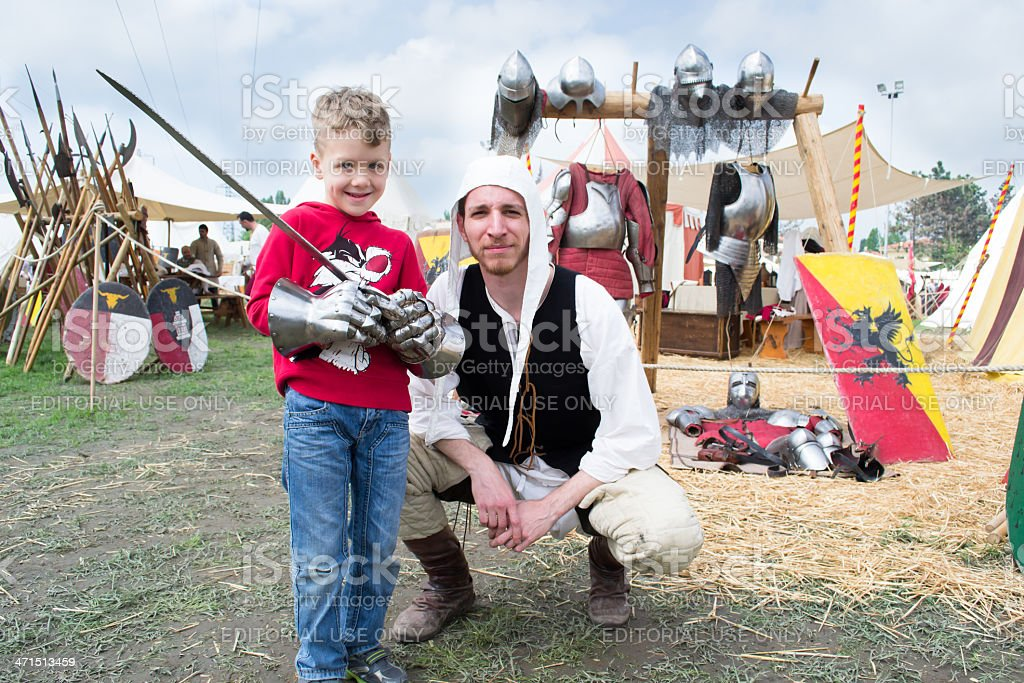 Knight shows the parts of medieval armor to a child royalty-free stock photo