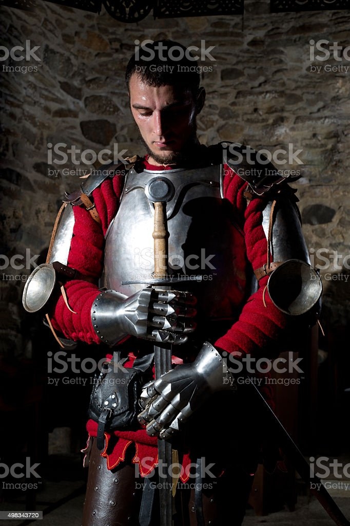 Knight Standing With Head Bowed in Prayer and Holding Sword stock photo