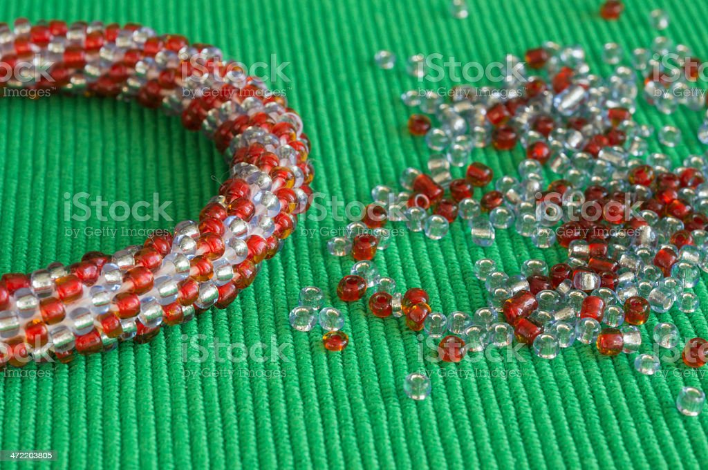 Knitted bracelet and the scattered beads on a green background royalty-free stock photo