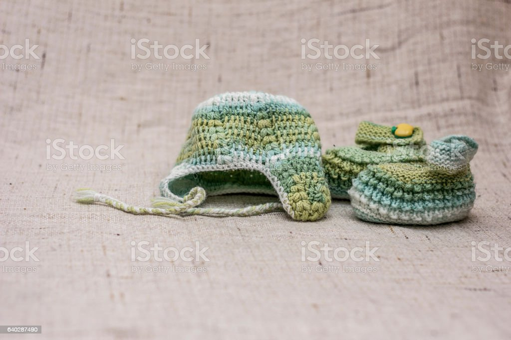 Knitted cap and booties for the baby stock photo