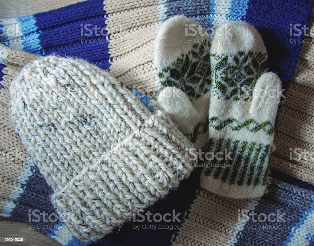Knitted cap and mittens on a wooden background stock photo