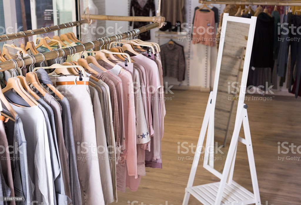 Knitted clothing on hangers in garment store stock photo