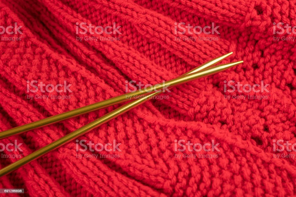 Knitted garment in red yarn and golden knitting needles stock photo