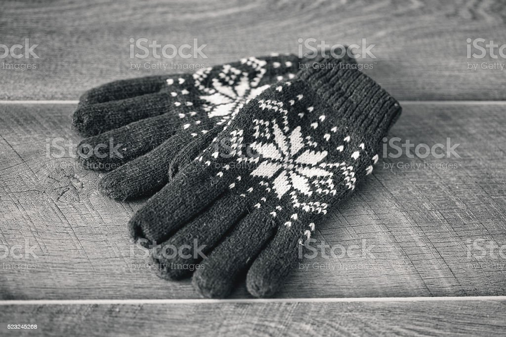 knitted gloves with embroidered snowflakes on wooden background stock photo