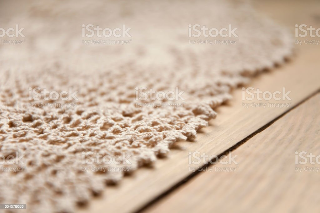 Knitted homemade white lacy doily on wooden background. Selective focus. stock photo