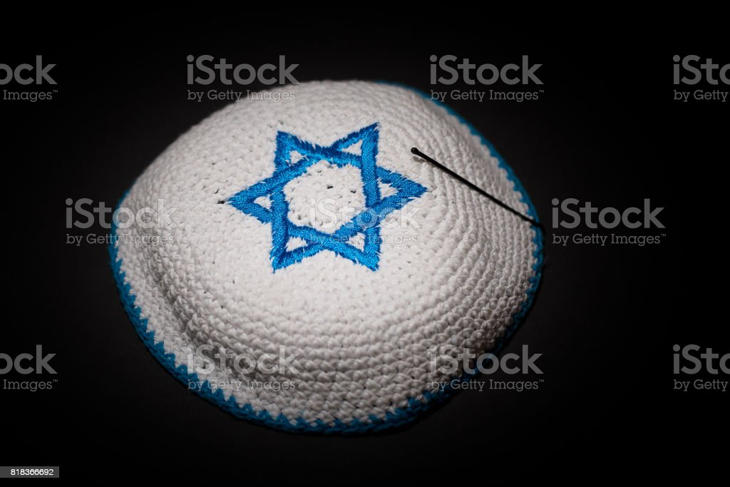 Knitted kippah with blue David star on black background close up. Seder concept stock photo