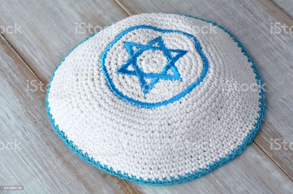 Knitted kippah with embroidered blue and white Star of David stock photo