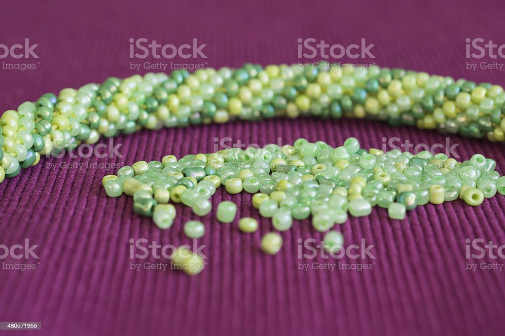 Knitted necklace and the scattered beads close up royalty-free stock photo