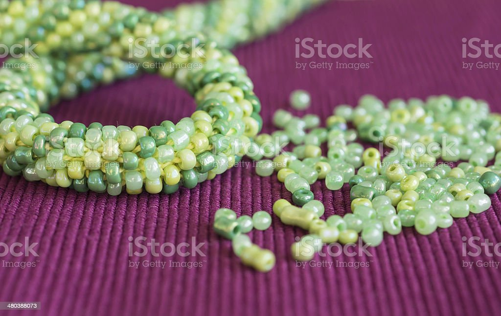 Knitted necklace and the scattered beads on a crimson background royalty-free stock photo