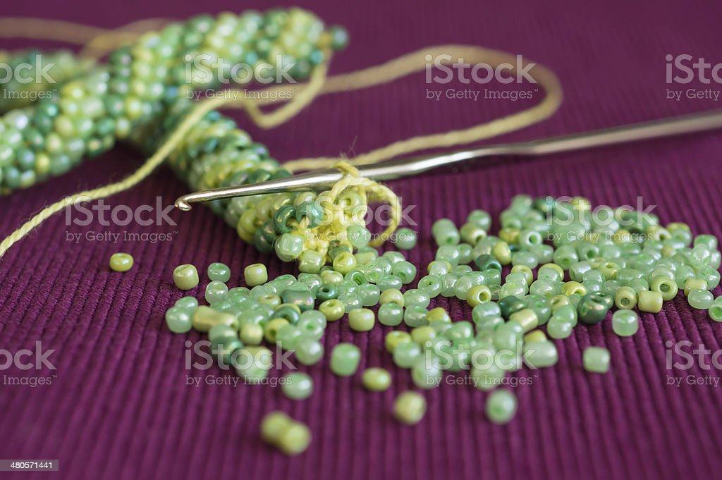 Knitted necklace and the scattered beads stock photo