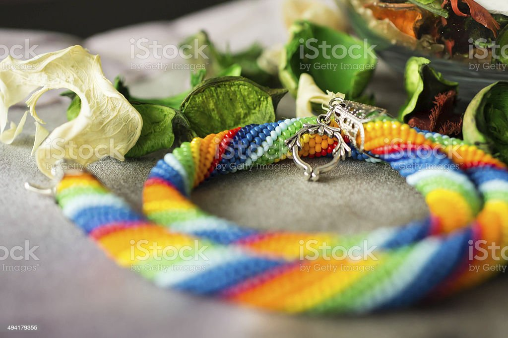 Knitted necklace from beads of a rainbow colors close up stock photo