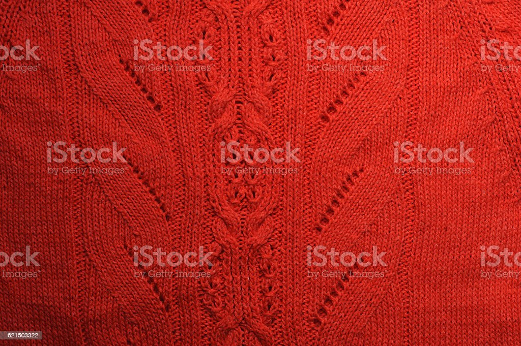 Knitted ornaments on coral fabric texture. stock photo
