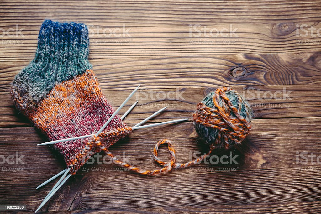 Knitted sock, ball of yarn and knitting needles stock photo