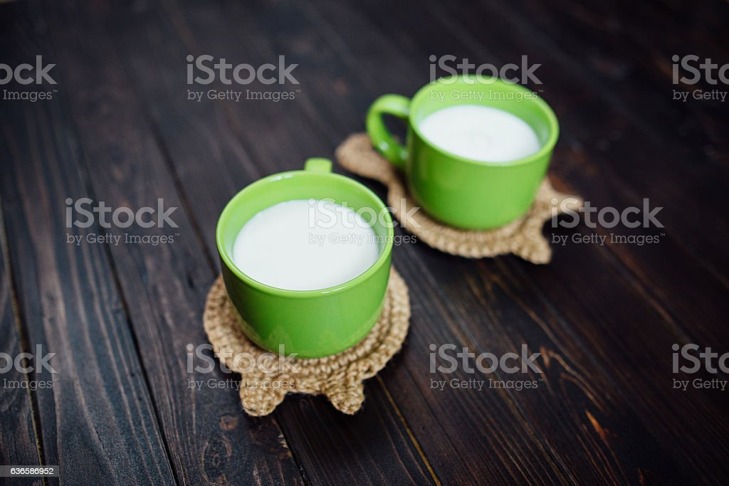 Knitted stand hot dishes and tea cups with , milk. Lying stock photo