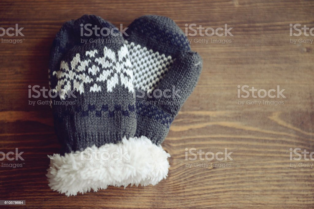 knitted woolen mittens on a wooden background stock photo