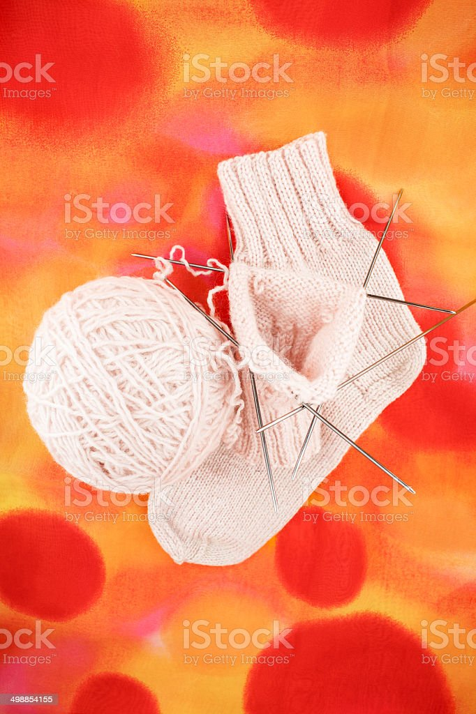 knitted woolen sock and spokes with a ball for knitting royalty-free stock photo