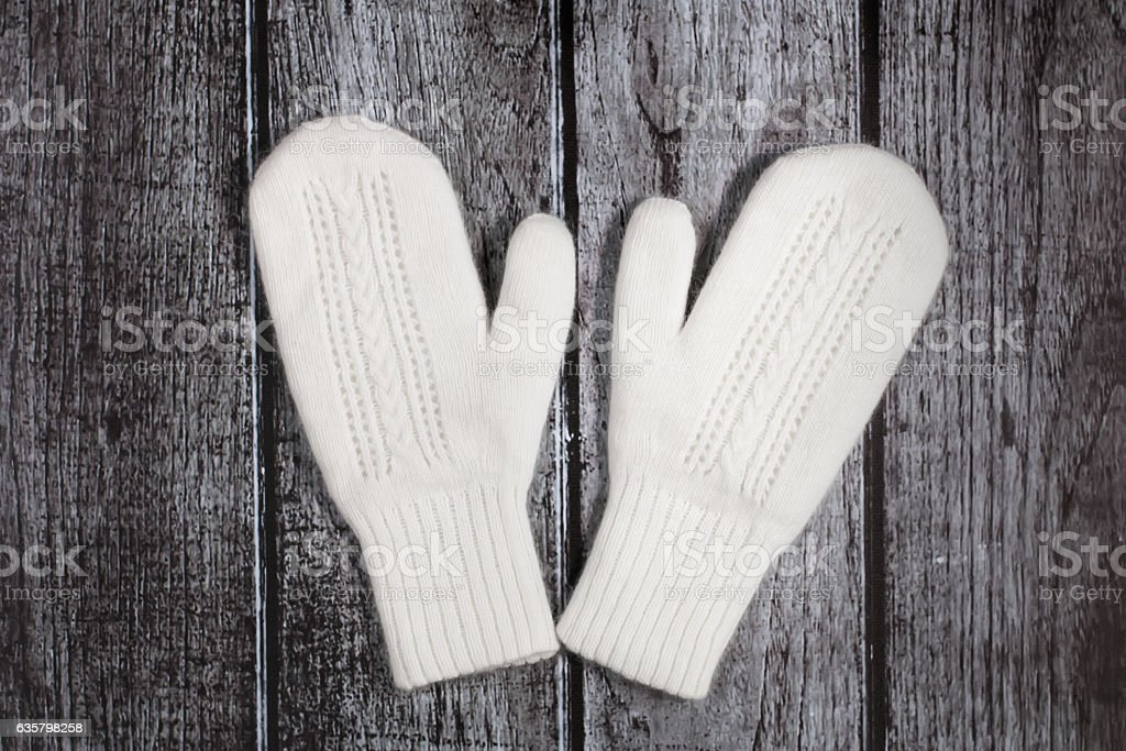 Knitted woolen white mittens on a rustic wooden background stock photo