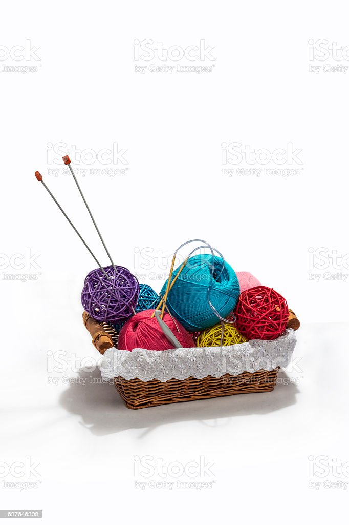 Knitting color yarn balls and needles in basket isolated stock photo