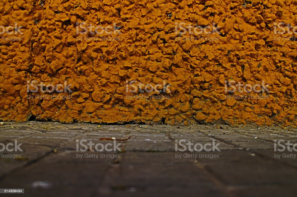 Knobbly Yellow Painted Wall and Pavement stock photo