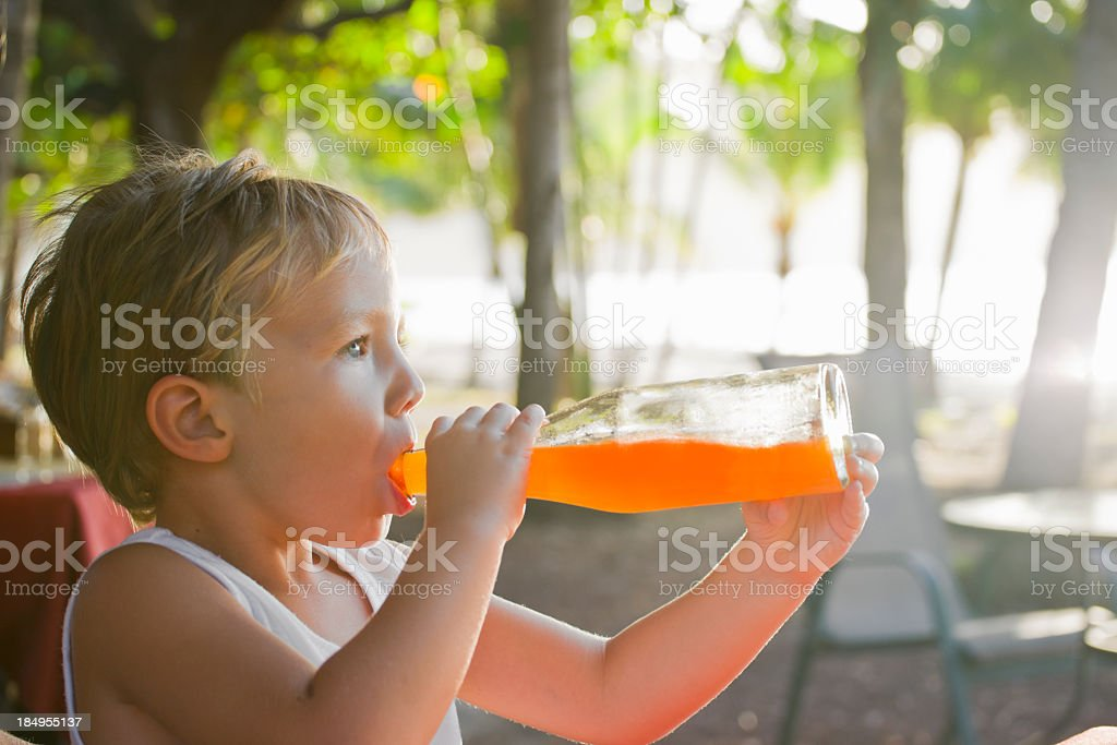Knocking it back at the beach bar, a child drinking. stock photo